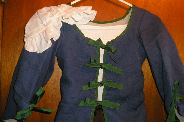 detail of frilled cap or bonnet and ribbon  binding and ties on jacket